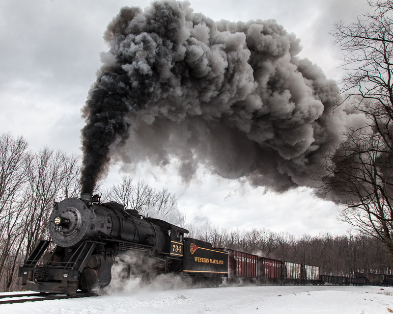 734 Western MD steam train spewing smoke and steam heading up the track