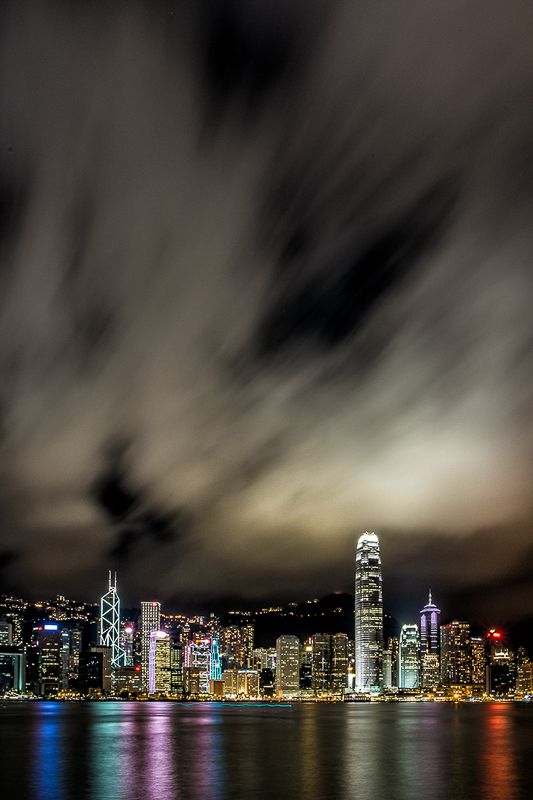Hong Kong harbor nighttime long exposure building lights and clouds vertical