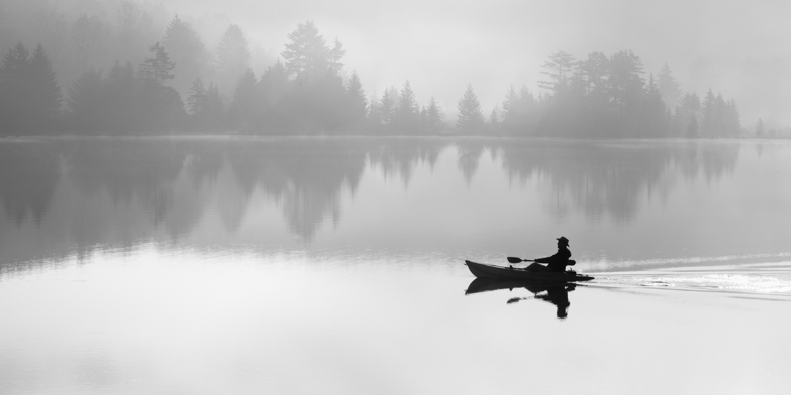 Black and white silhouette of a man kayaking of Spruce Knob Lake On a Foggy Morning