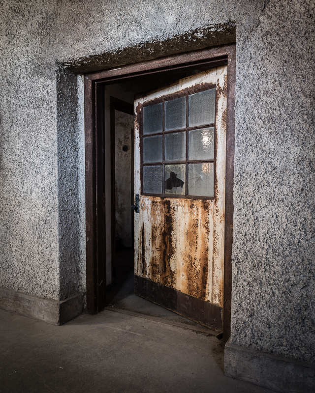 Large rusty door with broken window panes