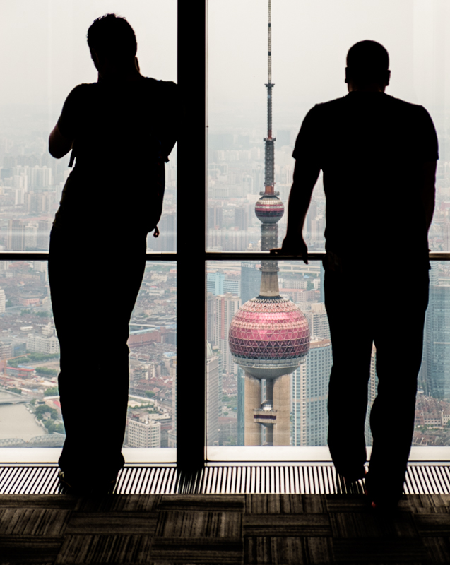 Men silhouetted looking out from Shanghai World Financial Center