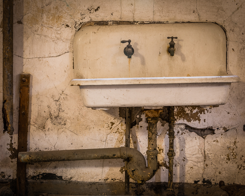 Rusty enameled sink and spigots