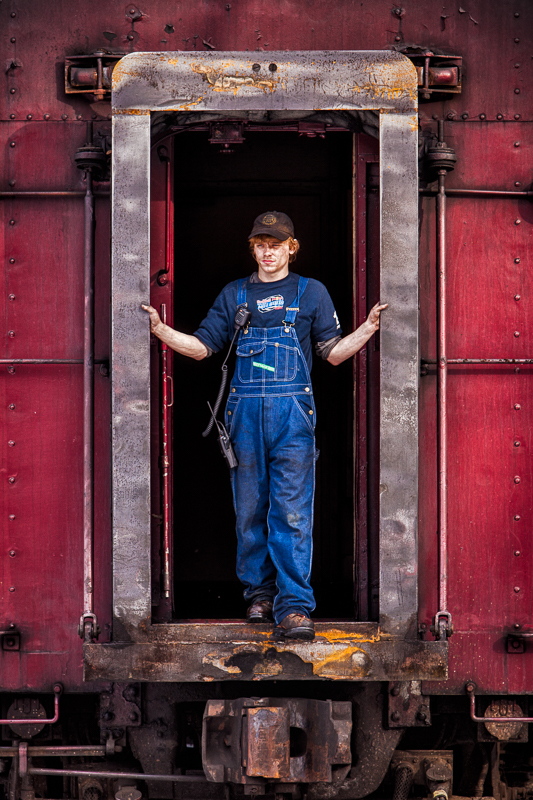Redheaded trainmen in red train car doorway with soot on his face in overalls waiting to couple the train
