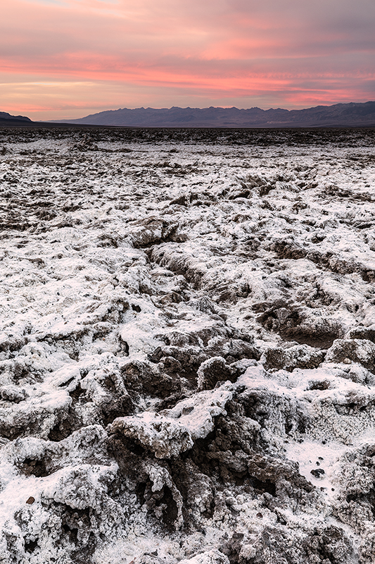 Death Valley playa with dark sunset sky and gnarly salt formations