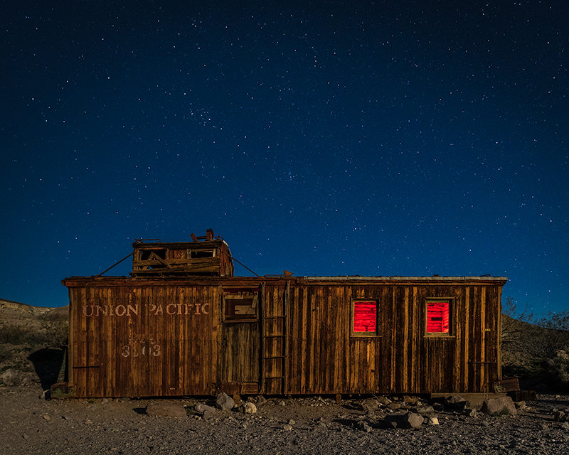Rhyolite caboose at night with starry sky