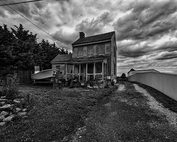 Abandoned house in Smyrna DE used to store commercial fishing equipment in black and white