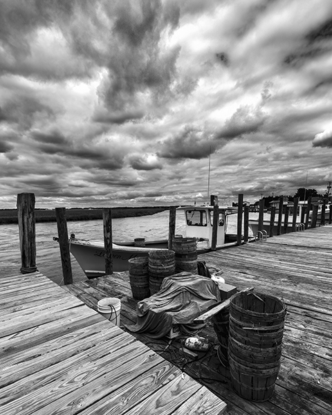 Smyrna working dock with dramatic sky fishing boat and crabbing equipment in black and white
