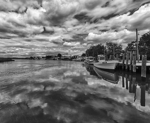 View from Sambo's Dock in Smyrna DE with fishing boats and dramatic sky and reflections in black and white