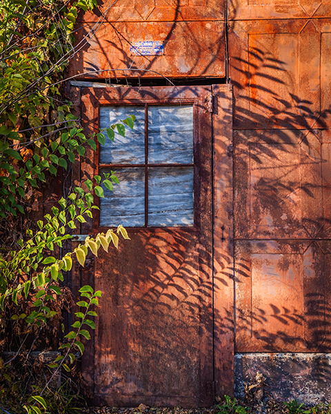 Rusty door with sun and shadows